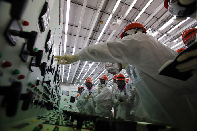 Members of the media and Tokyo Electric Power Co. (TEPCO) employees wearing protective suits and masks visit the central control room for the No. 1 and No. 2 reactors at the tsunami-crippled TEPCO's Fukushima Daiichi nuclear power plant in Fukushima prefecture March 10, 2014. (Reuters / Toru Hanai)