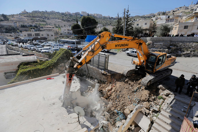 A bulldozer demolishes a house in Jabel Mukaber, a Palestinian village in the suburbs of East Jerusalem February 5, 2014. (Reuters / Ammar Awad)