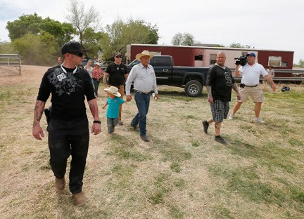 Rancher Cliven Bundy (C), with his grandson Braxton Louge in tow and armed security guards leave his ranch house on April 11, 2014 west of Mesquite, Nevada (AFP Photo / George Frey)