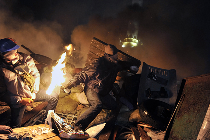 A protester hurls a molotov cocktail towards police from the barricades at Independence square in Kiev on February 19, 2014 (AFP Photo / Louisa Gouliamaki)
