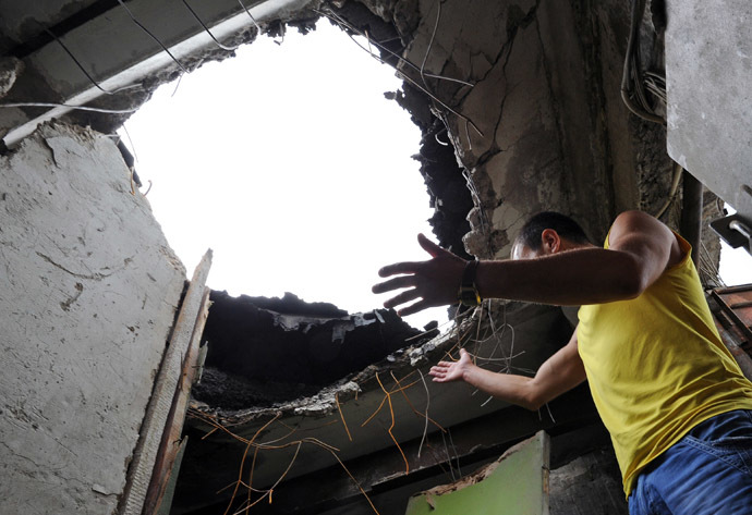 A resident looks at a hole on July 9, 2014 in the ceiling of his apartment, in a building damaged the day before by Ukrainian forces' mortar fire, in Lugansk, eastern Ukraine (AFP Photo)