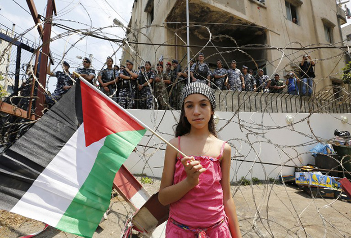A girls holds up the Palestinian flag during a protest near the US embassy in Awkar, on the outskirts of the Lebanese capital Beirut, on July 20, 2014, against the Israeli military offensive on the Palestinian Gaza Strip. (AFP Photo / Anwar Amro)