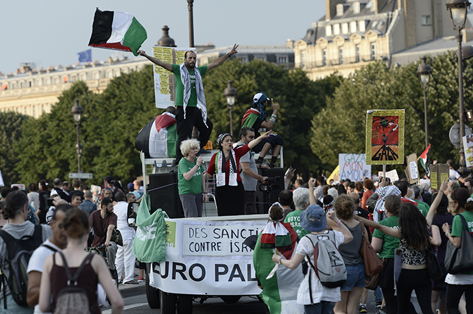 Protesters wave Palestinian flags as they stand on a vehicle during a demonstration on July 23, 2014 in front of the Invalides in Paris, to denounce Israel's military campaign in Gaza and to show their support to the Palestinian people (AFP Photo / Stephane De Sakutin)