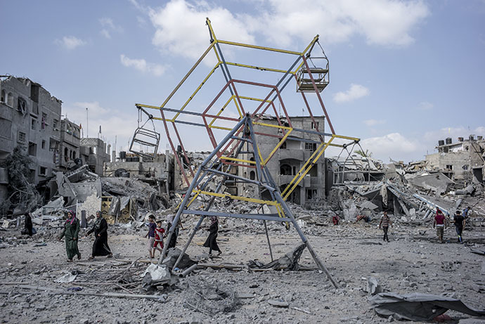 Palestininans go their way past rubbles and a mini ferris wheel in the northern district of Beit Hanun in the Gaza Strip, during an humanitarian truce, on July 26, 2014. (AFP Photo / Marco Longari)