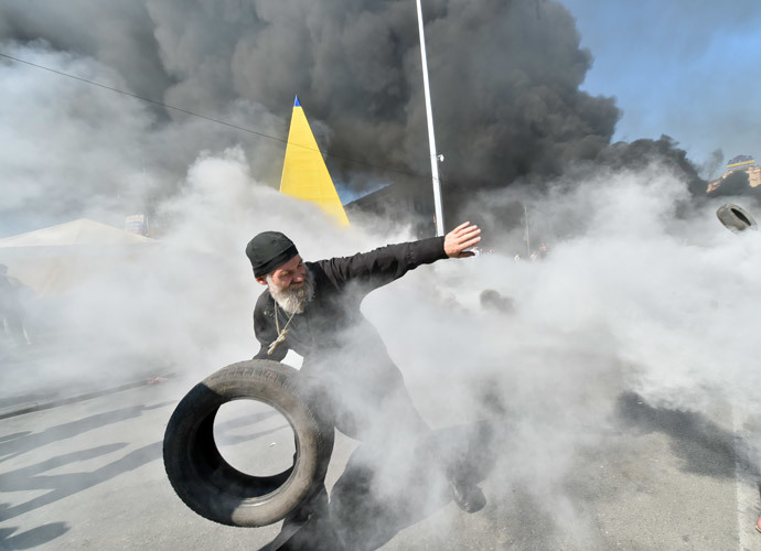 An Orthodox priest throws a tyre as Maidan self-defence activists clash with fighters of Kiev-1 volunteer battalion on Independence Square in Kiev on August 7, 2014.(AFP Photo / Sergei Supinsky )