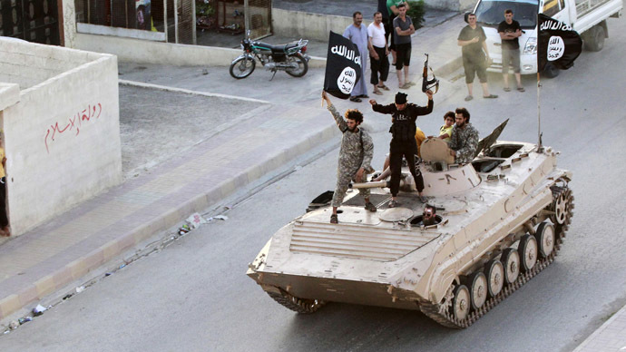 Militant Islamist fighters take part in a military parade along the streets of northern Raqqa province June 30, 2014 (Reuters)
