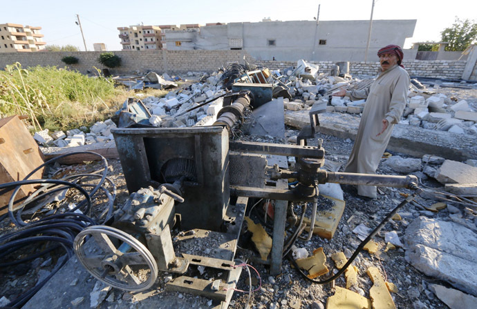 Abu Ismail, the owner of a plastics factory that was targeted on Sunday by what activists said were U.S.-led air strikes, gestures while standing at his destroyed factory in the Islamic State's stronghold of Raqqa September 29, 2014. (Reuters/Stringer)