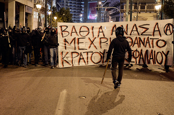 """Anarchists carry a banner reading """"Deep breath until the death of the state and the capital"""" in Athens on December 2, 2014 during a massive march in solidarity with a 22-years old anarchist hunger striker, Nikos Romanos (AFP Photo / Louisa Gouliamaki)"""