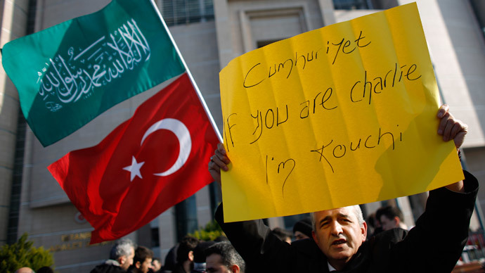 A demonstrator holds a banner as others wave Turkish and Islamic flags during a protest against Cumhuriyet, a staunchly secular opposition newspaper, in Istanbul January 15, 2015.(Ruters / Murad Sezer)
