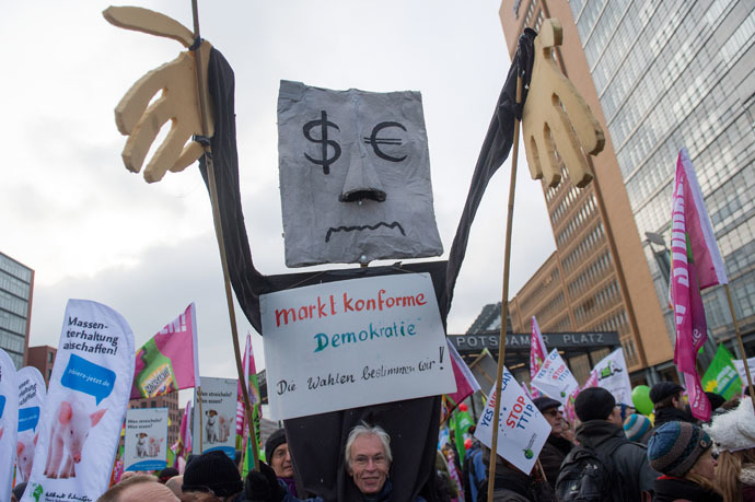 "A protestor holds up a figure with a sign reading ""market-compliant democracy- we rule elections"" (marktkonforme Demokratie- Die Wahlen bestimmen wir) during a demonstration against the TTIP (Transatlantic Trade and Investment Pact) in Berlin, on January 17, 2015. (AFP/DPA)"