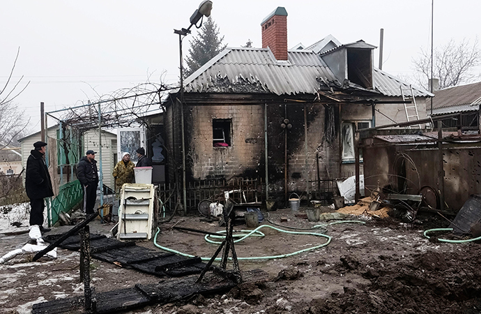Local residents inspect their home, which was damaged by shelling in the village of Sartan, near Mariupol (Reuters / Nikolay Ryabchenko)