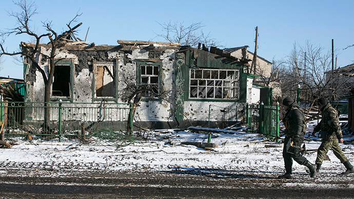 Rebels walk near a building damaged during fighting in the village of Nikishine, south east of Debaltsevo February 17, 2015 (Reuters / Baz Ratner)