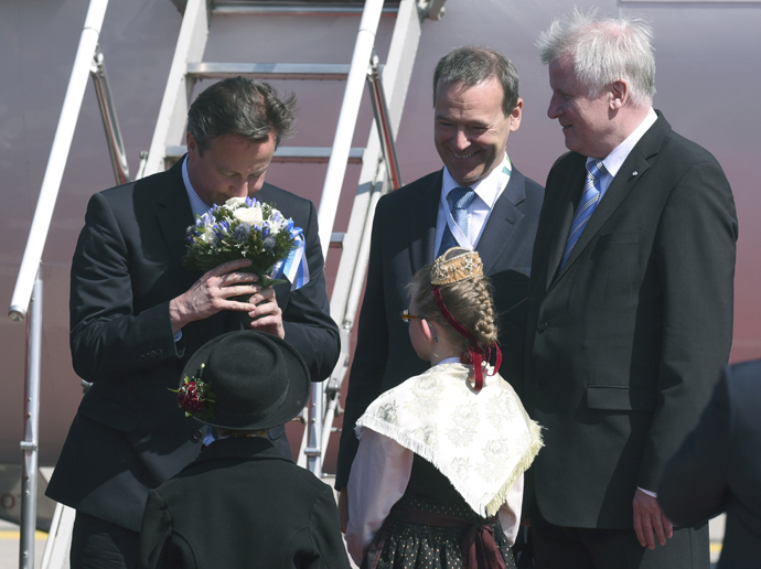 British Prime Minister David Cameron (L) receives flowers from children during a welcoming ceremony at Munich airport, Germany, June 7, 2015. (Reuters / Lukas Barth)