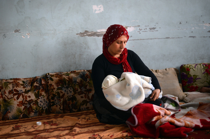 A Syrian Kurdish refugee from the majority-Kurdish Sheikh Maqsud district of the northern Syrian city of Aleppo, holds her baby in a school used as a refugee camp in the northern city of Afrin (AFP Photo / Dimitar Dilkoff)