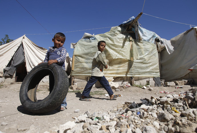A Palestinian refugee boy from Syria plays with a tyre as another boy walks past tents at Ain al-Helweh Palestinian refugee camp near the port-city of Sidon, southern Lebanon (Reuters/Ali Hashisho)