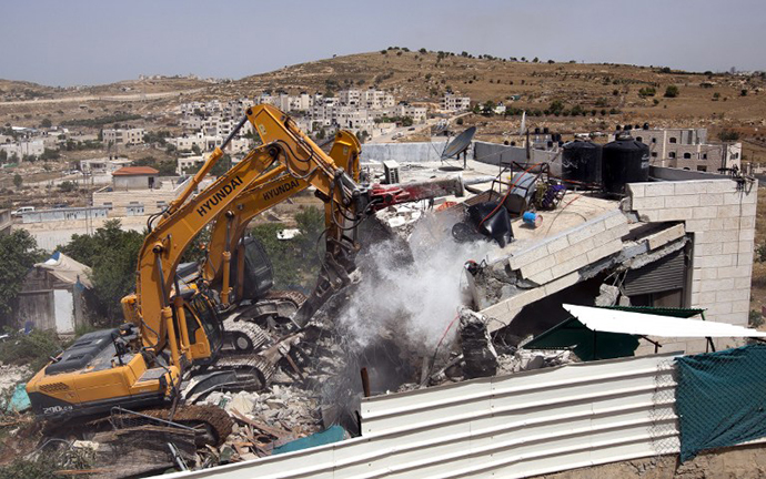 Israeli municiplaity bulldozers destroy a Palestinian house in the Arab east Jerusalem neighborhood of Beit Hanina, on May 29, 2013. (AFP photo / Ahmad Gharabli)