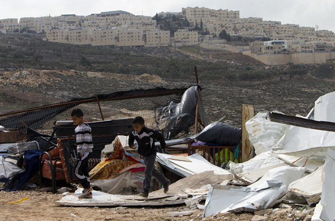 Palestinian children walk through the rubble of a house demolised by the Israeli authorities for being built without municipal permission in the Arab east Jerusalem neighborhood of Beit Hanina on January 27, 2014, with the Jewish settlement of Ramat Shlomo in the background. (AFP Photo / Ahmad Gharabli)