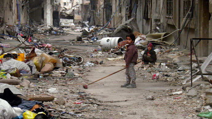 A child clears damage and debris in the besieged area of Homs (Reuters / Thaer Al Khalidiya)