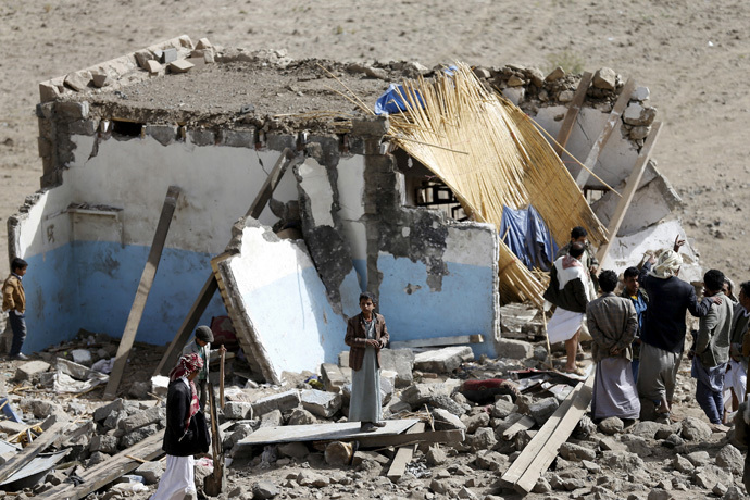 People gather on the wreckage of a house destroyed by an air strike in the Bait Rejal village west of Yemen's capital Sanaa April 7, 2015. (Reuters/Khaled Abdullah)
