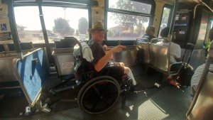 A man using a wheelchair rides on a public bus.