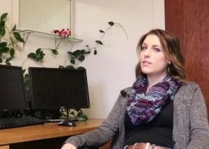 Arynn Payne seated at her desk.