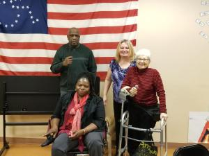 Four people pose in front of a disability rights flag. Three of the people have visible disabilities.