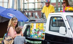 A man operates an ice cream truck at an outdoor farmers market. He is an amputee.