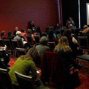 workshop participants listening to a panel of speakers