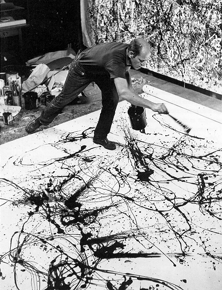 [Black and White Photograph of Artist Jackson Pollock at work dripping Paint onto a canvas]