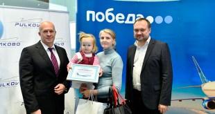Генеральный директор 'Подебы' Андрей Калмыков (слева) и коммерческий директор аэропорта Пулково Евгений Ильин (справа) поздравили юбилейного пассажира