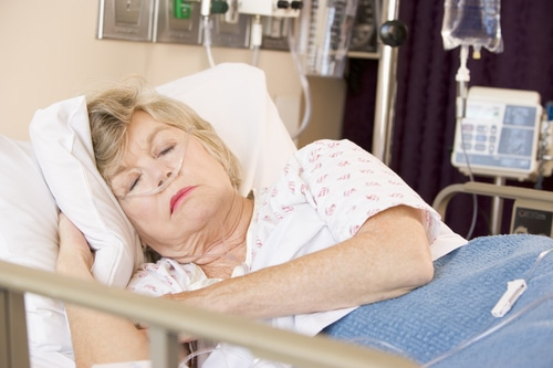 Senior Woman Sleeping In Hospital Bed