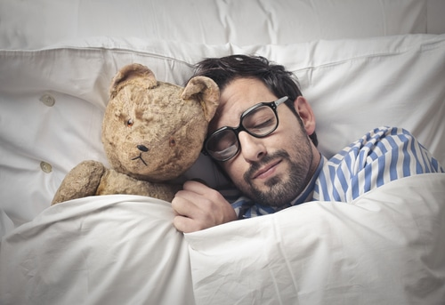 man sleeping with teddy bear