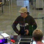 Этот грабитель угрожает банкирам пистолетом (фото камеры наблюдения).