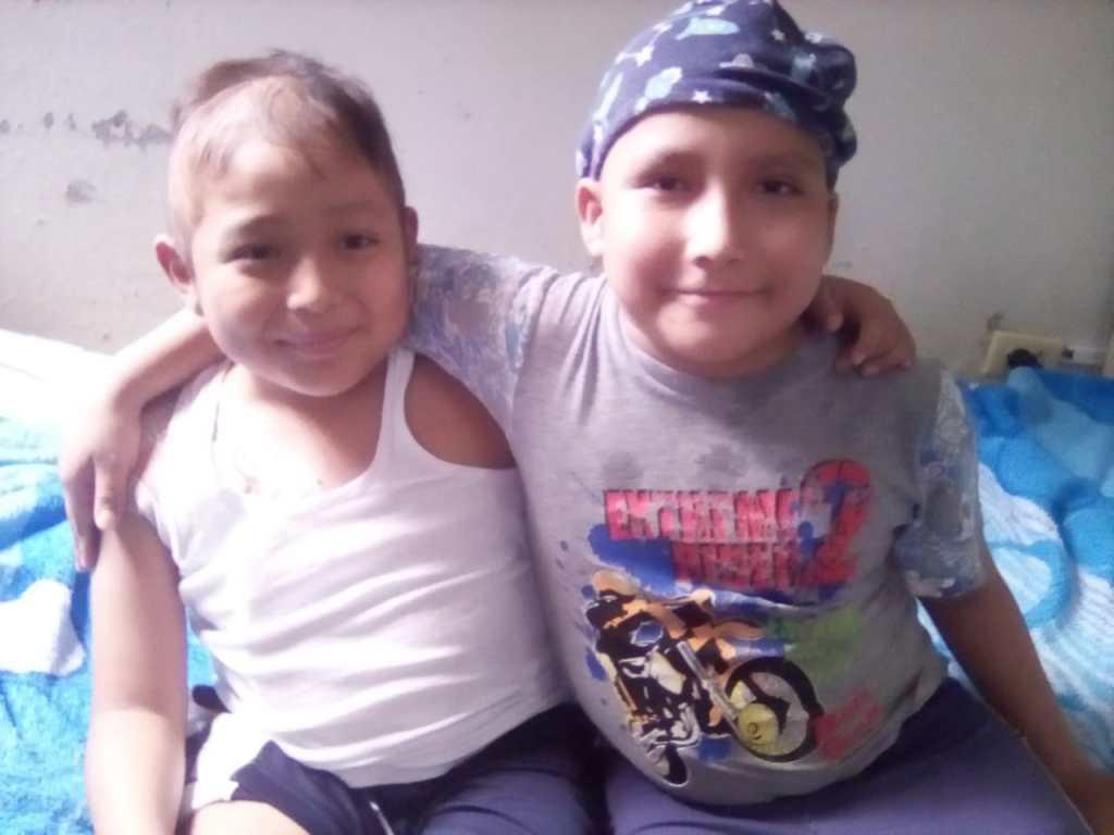 Zwei Leukämiekranke Jungen sitzen im Krankenhaus in Peru auf einem Krankenhausbett.