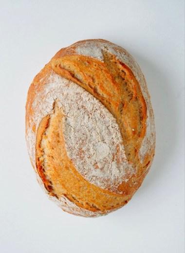 Dieses Foto zeigt das ovale, schön gebräunte Brot von Oben. Es besitzt zwei leicht geschwungene, schräge einschnitte auf denen sich kein Mehl befindet. In der Mitte des Brotes entsteht dadurch eine schöne ellipsenförmige mit Mehl bestäube Fläche, die sich optisch vom knusprigen Brot abhebt.