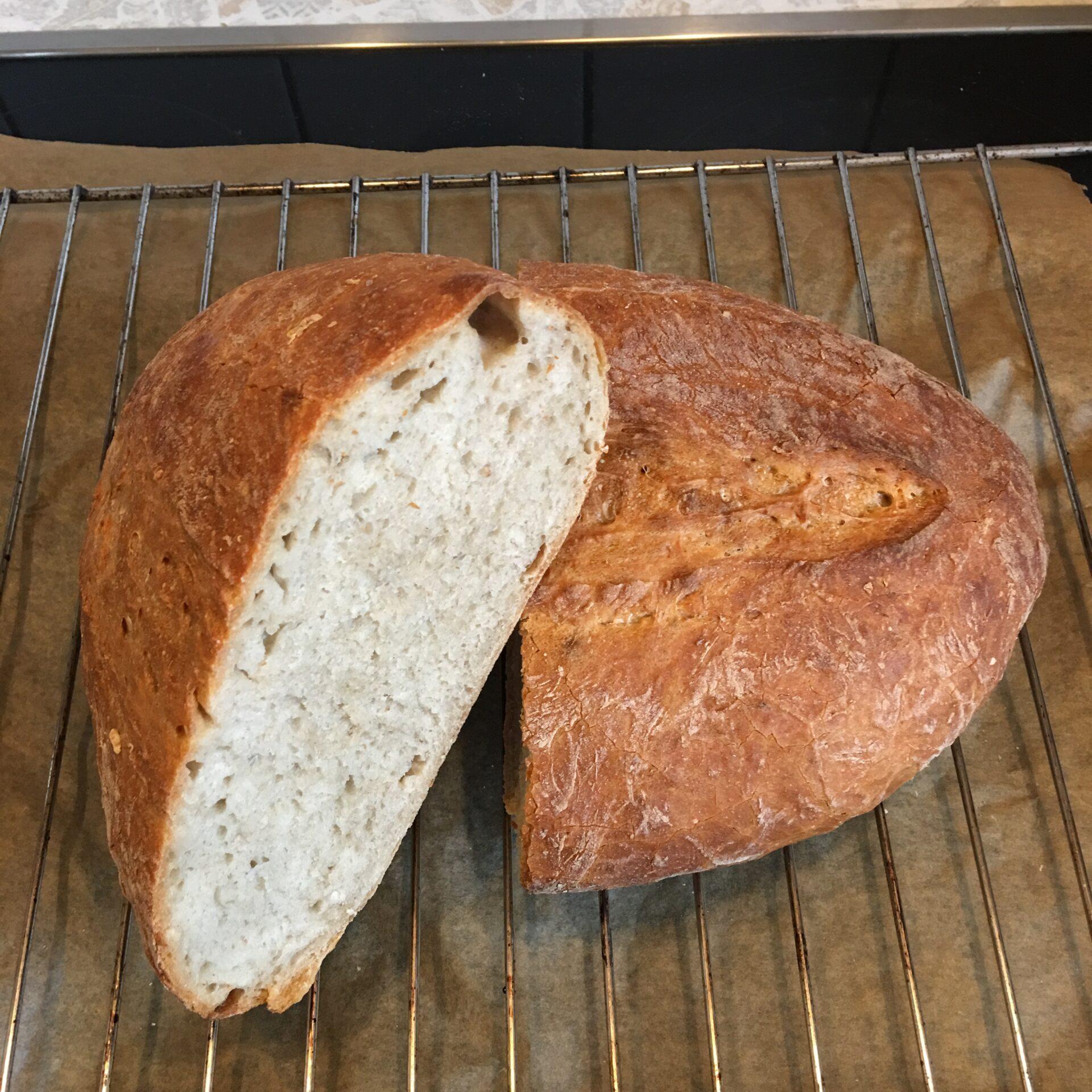 Ein halbiertes Brot. Man kann sowohl die Kruste, als auch die weiche Krume fühlen.