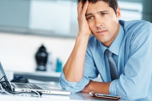 Businessman sitting at desk with hand on his face, looking worried