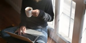 woman using laptop while holding a cup of coffee 3759083 2