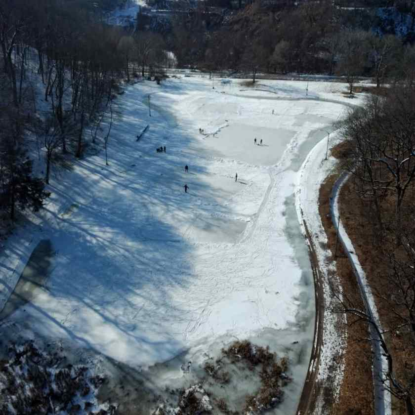 Looking down at frozen, snow covered pond with skaters and hockey players on it on a sunny afternoon.