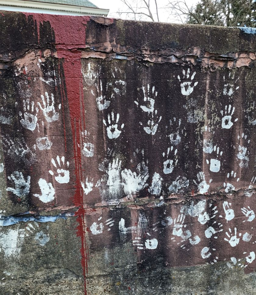 White handprints on a stone wall