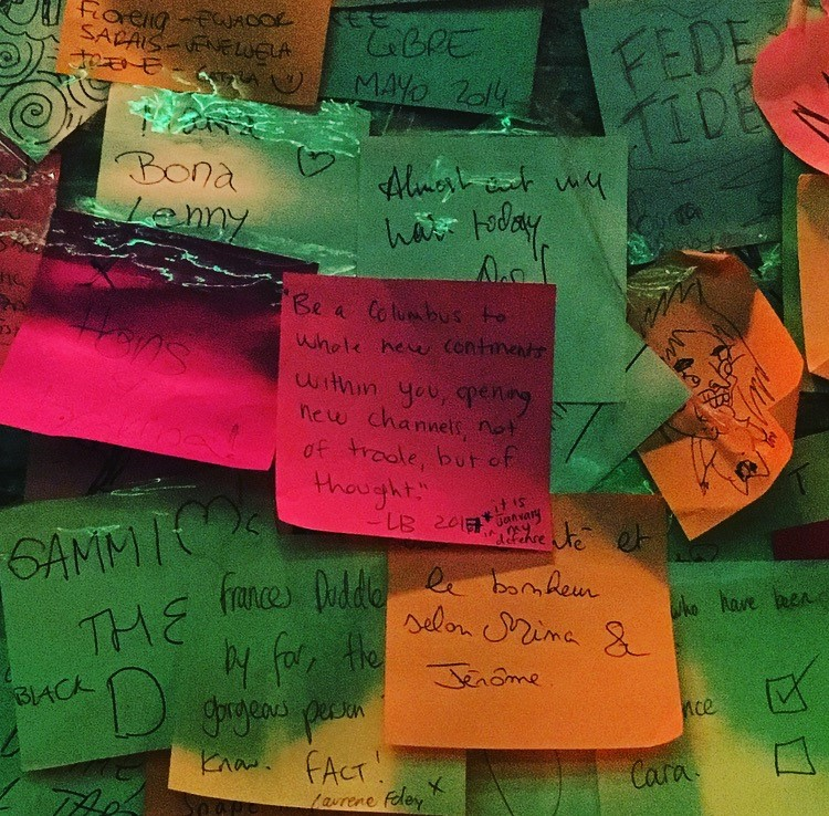 "Colourful post it notes are layered on the walls. ""Be a Columbus to whole new continents within you, opening new channels not of trade, but of thought"" is centred."