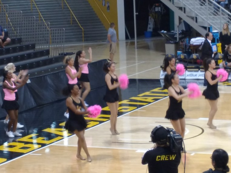 Long Beach State dance team on the court inside The Pyramid and using pink pom-poms for Breast Cancer Awareness night