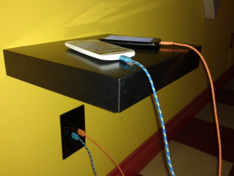 Image of phones charging with USB Cables plugged directly into wall outlets