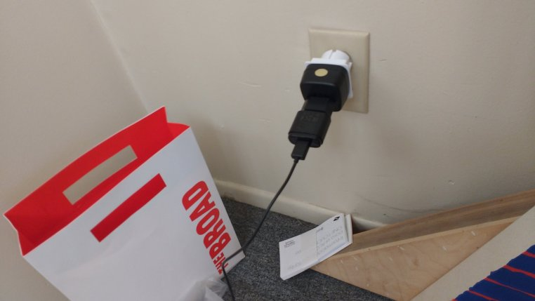 photo of a string of international power adapters sticking out of a USA wall socket