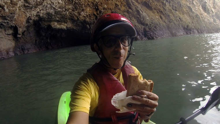 Glenn Zucman in a kayak eating a sandwich inside a sea cave at Santa Cruz island, California Channel Islands