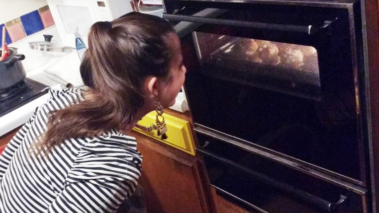 Terézia looking through the oven window to check the status of the baking chouquettes