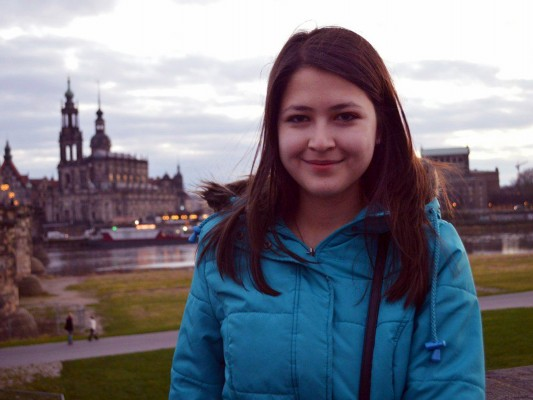 Aylar in a winter coat standing in front of a Dresden panorama