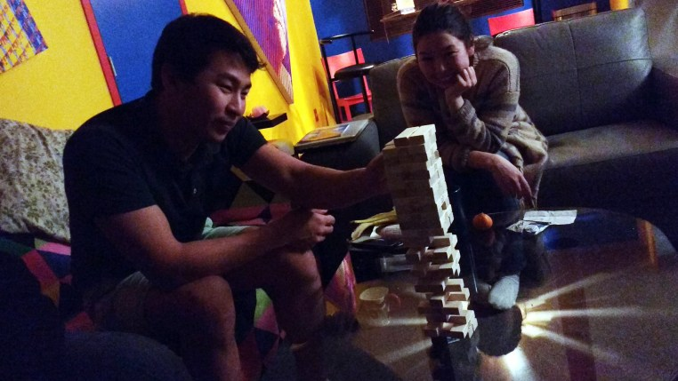 sitting in the living room playing Jenga