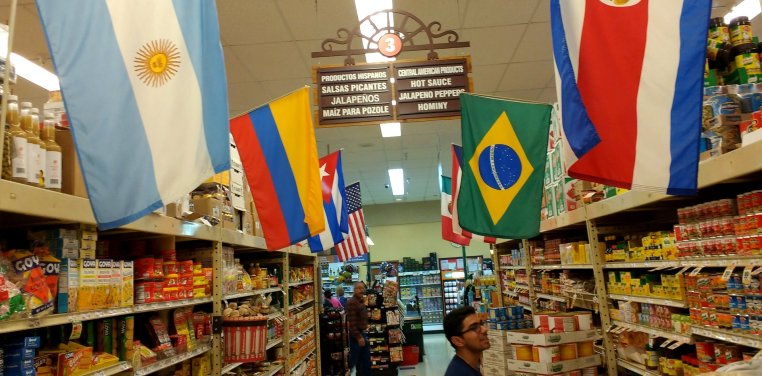 Davis in a grocer store aisle. The shelves are topped with international flags