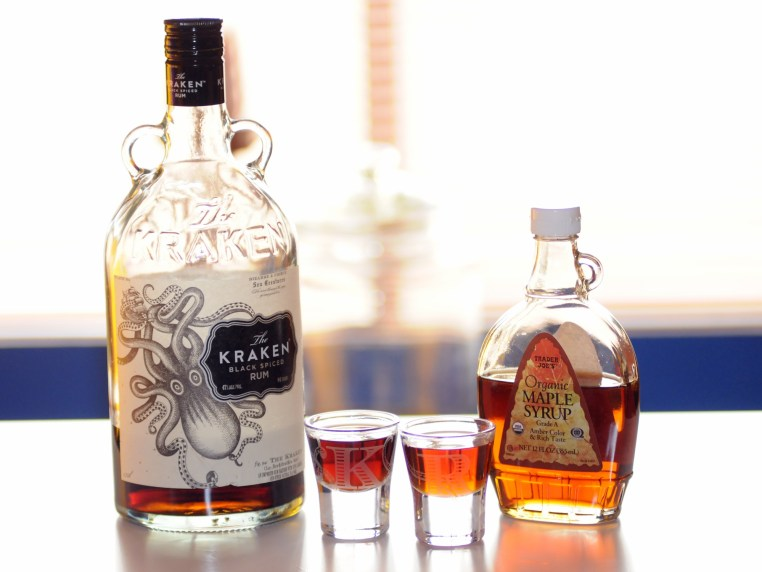 a bottle of Kraken Rum, a bottle of Maple Syrup, and two shot glasses, each with one of the liquids in it